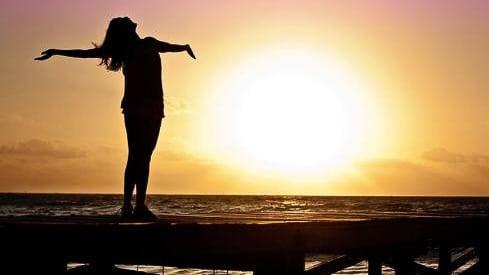 Femme sur ponton avec couché de soleil